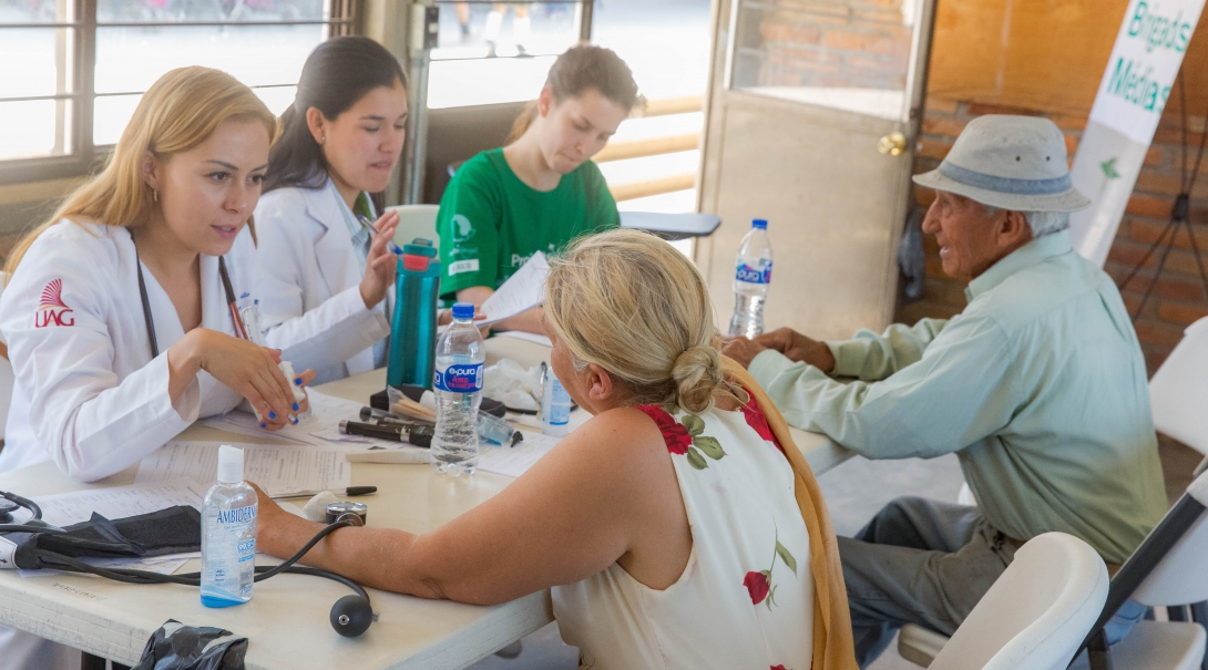 Interns measure blood pressure as part of their public health work in Mexico with a group.